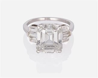 1010 An Art Deco Diamond Ring Circa 1925, platinum Weighing 6.46ct with GIA certificate stating F color and VS2 clarity, flanked by 6 baguette-cut diamonds totaling approximately 0.8ct, and graded F-G color and VS clarity Ring size: 6.25 5.5 grams 2 pieces Estimate: $120,000 - $180,000