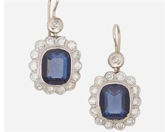 """1006 A Pair Of Simulated Sapphire And Diamond Earrings 14k white gold Set with two simulated sapphire ear pendants surrounded by thirty single and full-cut round diamonds totaling approximately 1.5ct, and graded H-J color and SI-I clarity 1.40"""" L x 0.75"""" W 55 grams gross 2 pieces Estimate: $800 - $1,200"""