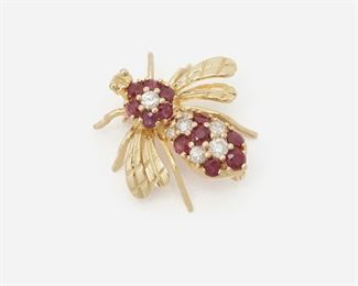 """2001 A Ruby And Diamond Bee Brooch 14k yellow gold Set with seven full-cut round diamonds totaling approximately 0.40ct and graded H-I color, SI clarity, and further set with twelve round rubies totaling approximately 0.80ct .875""""W x .875""""H 3 grams Estimate: $600 - $800"""