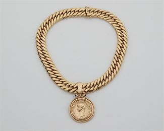 """2005 A Gold Coin Style Pendant Necklace 14k yellow gold Suspending a detachable pendant styled as a coin topped with two round sapphires 16"""" L x 2.5"""" H 118.9 grams 2 pieces Estimate: $3,000 - $5,000"""