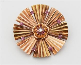 """2009 A Retro Ruby And Diamond Pinwheel Brooch Circa 1940, 14k rose & yellow gold A stylized pin-wheel style brooch centering one full-cut round diamond gauged at approximately 0.10ct and graded G-H color, VS clarity, and further surrounded by fourteen round rubies totaling approximately 0.70ct 2"""" W 22 grams Estimate: $800 - $1,200"""