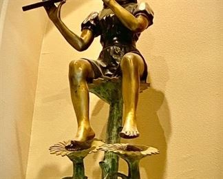 JUMBO GIRL WITH FLUTE By Herbert. Bronze Size: 57 in. h x 31 in. l x 17 in. is a premium outdoor sculpture. The life size sculpture weighs 100 lbs. shows a little girl playing a flut, sitting on top of a sunflower blossom with two other sunflowers located below.  Bronze with Multi-color patina. $1500