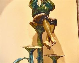 Brass. Size: 57 in. h x 31 in. l x 17 in. is a premium outdoor sculpture. The life size sculpture shows a little boy playing a piccolo, sitting on top of a sunflower blossom with two other sunflowers located below. Bronze with Multi-color patina. Asking $1200 Retail ($2800)