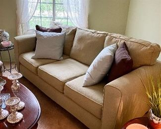 Comfortable 3-cushion couch in clean, neutral fabric.