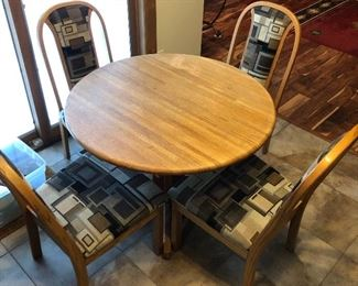 Dining table with four chairs and two additional leaves (not shown).