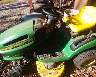 John  Deere  riding mower with tow cart sold as is.