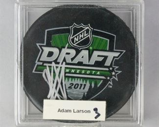 12	Adam Larsson Autographed 2011 NHL Draft Puck	Signed Adam Larsson 2011 NHL draft puck, in protective case