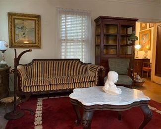 Velvet settee, marble top coffee table, and a red cabinet with chicken wire
