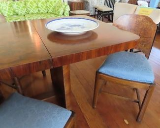 Mid Century Burled Wood dining table  with 4 matching chairs.   The table to rests on a base of curved burled wood columns.