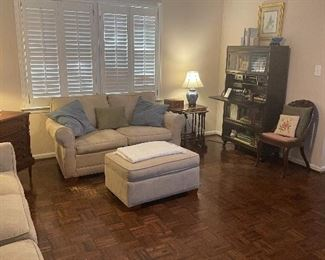 Sofa, loveseat set with ottoman, nesting tables, barrister bookcase, lamp, multiple pillows, antiques.