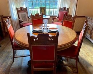 Antique Empire Style Quarter Sawn Oak Pedestal Dining Table features lavish baroque carved claw feet and lions' head on chairs upholstered in a plush orange-red velvet. Exquisite 9-PC set includes: pedestal table, extra leaves, and 8 chairs (6 parlor, 2 arm chairs)
