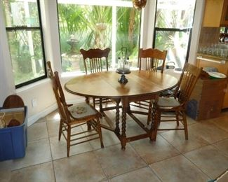 A small round dinning room table with 4 matching chairs nice oak and solid.