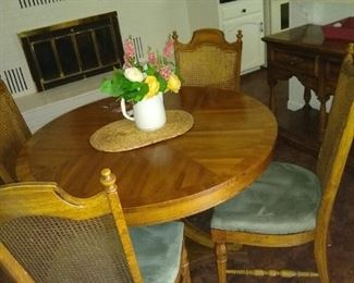Beautiful grained wood dining table with chairs. Four chairs on the property and leaves for expansion.