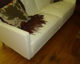 Modern white vinyl sofa with wooden legs tufted seats and back like new.