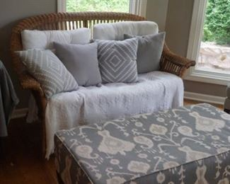 Wicker loveseat and modern ottoman with pillows
