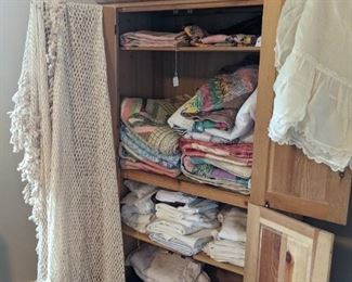 pine cupboard filled with old quilts and nice linens