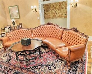 Ornately carved semi circular tufted leather sofa from the lobby of the Hotel Montaleone in New Orleans