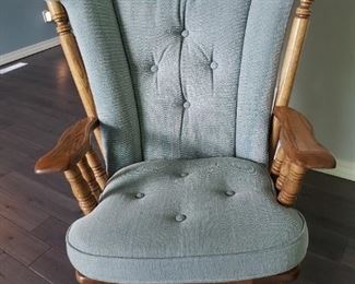 High quality oak glider rocker with sage colored cushions.