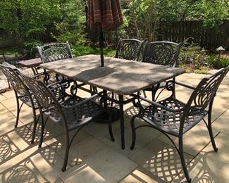 Cast aluminum patio dining chairs and table with faux slate veneer top. California patio umbrella