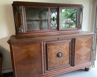 Beautiful German antique sideboard, great carved details, beveled glass doors and pull out marble top serving area.