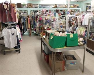 Individually priced clothes (lots are brand new), vintage table with art magazines on top, flags, tablecloths, household items and baby and toddler clothes.