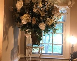 Wrought iron plant stand with large silk flower arrangement