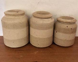 "$100 -  Set 3 stoneware cannisters with lids.   Left (large): 7"" H, 5"" diam. Center (medium): 6.75"" H, 4.75"" diam.  Right (small): 5.75"" H, 4.25"" diam."