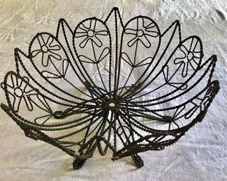 "$75 Black metal wiry daisy basket .25"" H, 15.75"" diam."