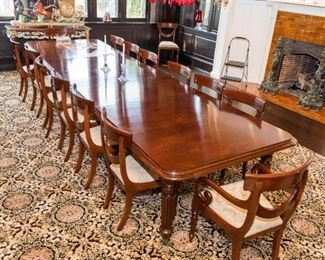 An English Regency style flame mahogany dining suite comprising a table with 4 leaves and 18 chairs.  Table H 28 1/2 x W 169 x D 50 inches.  Chairs H 34 1/2 x W 20 x D 17 inches.  $14,000.00