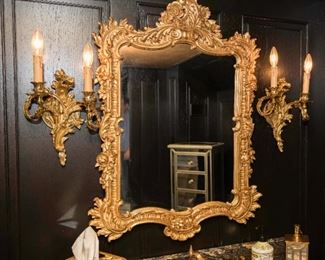 A Pair of Louis XV Style Gilt Metal Sconces and Gilt Wood Mirror.  Dimensions: Sconces Height 12 x width 8 ½ inches. Mirror Height 37 x width 23 ½ x depth 1 1/5 inches. Sconces $1,000.00 Mirror $600.00