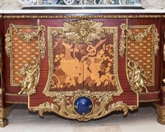 A Louis XIV Style Commode in the Manner of Jean Louis Riesener. Probably Twentieth Century. No Marks Evident.   The commode in the Louis XIV style and of demilune form having a demilune top with conforming white marble slab over the case, the edge with applied brass egg and art molding over multiple marquetry inlaid panels bracketed by large yellow metal figures, floral and foliate swags and putti; the center with two cabinet doors bracketed by applied yellow metal cornucopia and mask with sunburst rays and applied cerulean blue orb, raised on tapered feet with applied yellow metal acanthus leaf decoration. Dimensions: Height 39 x width 98 x depth 29 inches.  $45,000.00