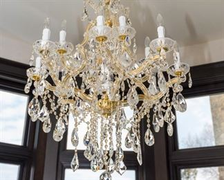 A Baccarat Style Leaded Glass and Brass Twelve Light Chandelier. Circa 2010-2013.   The chandelier in the Baccarat style having 12 electrified lights with clear glass swag tubes over brass tubing and multiple drops and swag jewels.  Dimensions: Height 36 x width 32 inches. $2,500.00