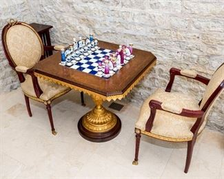 A Pair of Louis XVI Style Fauteuils. Circa Last Quarter of the Twentieth Century. No Marks Evident. The pair of fauteuils in the Louis Seize style with embellished yellow metal accents in the form of a wreath and ribbon finial at crest rail and applied metal accents to the skirt together with a Tiche burl walnut and gilt wood chess table having inset porcelain chess board, Tiche porcelain chess pieces and raised on a vasiform gilt wood standard ending on a round plinth.  Dimensions: Chairs Height 40 ½ x width 23 x depth 18 inches. Table Height 30 ½ x width 32 x depth 32 inches.   For the suite $8,000.00