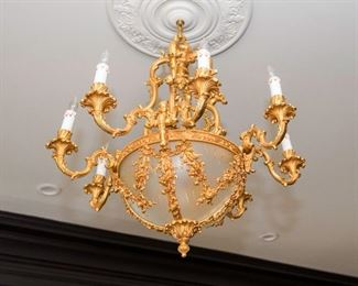 A Restauration Style Gilt Metal and Glass Eight Candle Chandelier. Circa 2010-2013. No Marks Evident. The chandelier in the Restauration style having git metal surface overall with eight electrified candles set on scrolled arms, the arms emanating from the convex glass bowl set in floral, foliate and ribbon swag. Dimensions: Height 36 x width 32 inches approximately.   $3,000.00
