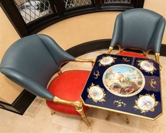 6An Empire Style Table and Leather Upholstered Chairs. Tiche. Italy.   TheTiche table in the French Empire style having an enameled top with inset porcelain placques, the center medallion with Tiche mark and depicting a classical scene of putti surrounded by four medallions with figures in 18th century attire, raised on gilt medal winged figured joined by a medial shelf with white bisque porcelain sculpture of two female nudes ending on scrolled toes. The two chairs having blue and red upholstery with gilt wood frames. Dimensions: Table Height 31 x width 27 x depth 27 inches. Chairs Height 41 ½ x width 26 ½ x depth 24 inches.    For the suite $10,000.00