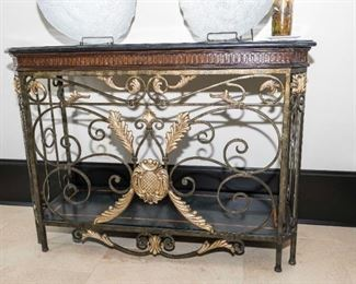 A French Style Marble and Wrought Iron Side Table. Circa 2005-2010. No Marks Evident.   The table of wrought iron composition, the shaped top with conforming black marble slab, the frame with scroll and gold painted acanthus leaf decoration.  Condition: Very Good. Dimensions: Height 36 x width 48 x depth 18 inches.  $1,500.00