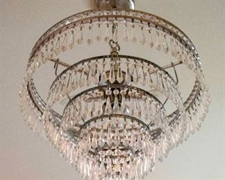 A Contemporary Five-Tiered Nickle and Leaded Glass Chandelier. Circa 2010-2013. The chandelier of plated nickel composition with five concentric graduated tiers having multiple prisms.  Condition: Very Good. Dimensions: Height 16 x width 22 inches approximately.                                                                                        $500.00