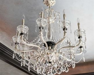 A  Baccarat Style Silver Gilt and Leaded Glass Ten Light Chandelier. Circa 2010-2013.  The chandelier in the Baccarat style having clear glass with colored glass accents, the scrolling arms with 10 electrified candles and supporting multiple jewel swags and drop Dimensions: Height 39 x width 36 inches.                            $2,500.00
