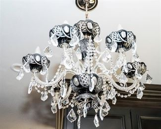 A Pair of Two Cut to Clear Six Light Chandeliers. Circa 2010-2013. The two chandeliers having six electrified candles with cut to clear black bobeches set on scrolled arms with multiple jeweled swags and drops. Dimensions: Height 24 x width 24 inches approximately.                                                                                 For the pair: $5,000.00  Each: $2,500.00