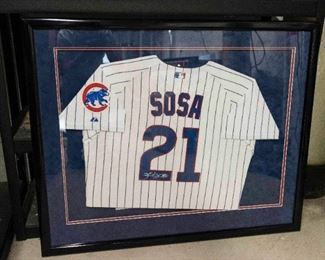A Framed and Signed Sammy Sosa Cubs Baseball Jersey. No Date.  Condition: Very Good. Dimensions: Frame 34 ½ x 42 inches.                                             $1,500.00