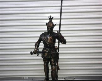 A Patinated metal sculpture in the form of a Medieval knight in armor with halberd. No Marks Evident.                   Height 50 inches to tip of halberd.                                                    $225.00