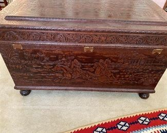 Handsome hand carved trunk with designs on all sides and top $750.00, horses, palm trees, places of worship