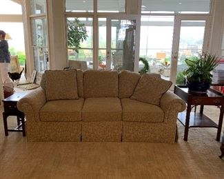 One of a pair of matching sofas and traditional side tables.