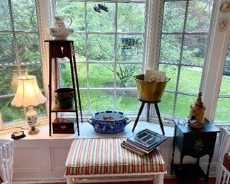 Sunroom bay window filled with small items & custom upholstered wicker ottoman.