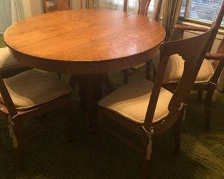 antique  solid oak table and 4 leaves -6 chairs- (5 armless- 1 with arms)  a few need some seat repairs- but overall very nice quality and condition