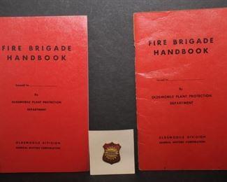 OLDSMOBILE FIRE BRIGADE HANDBOOKS AND CAP BADGE