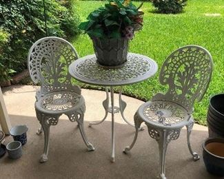Metal iron ornate outdoor table and assorted pots and planters