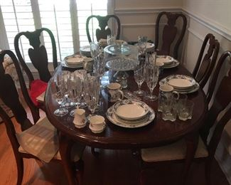 Classic dining room table with six chairs. Bone china. Table place setting. Vintage cake stand. Heavy crystal drinking glasses.