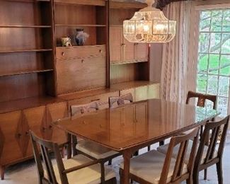 """Magnificent Mid Century Modern Dining room set, includes:  Table 60"""" x 40"""" 6 cane back chairs, leather seat cushions, 2 armchairs and 4 without arms Three wall cabinets, each is 36"""" x 19"""" x 80"""" tall Features two tone """"bowtie"""" veneers on the base doors and caned panel doors.  Beautiful wood grain throughout and original brass pulls. All in very good condition.  Table has been protected by a glass top. Ramseur Furniture Co., NC"""