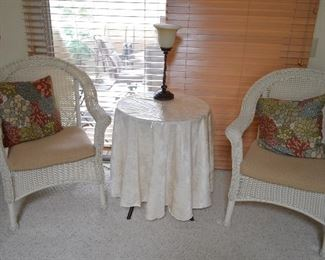 Wicker chairs, under that cloth another glass and metal table